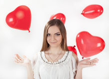 Young woman with red balloons. Young woman in white dress with   red heart shaped baloons. Valentine day concept, love concept Stock Photo