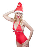 The young woman in red bathing suit and a red cap of Santa Claus on a white background Stock Photos