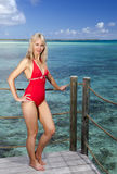 The young woman in a red bathing suit on sea background Royalty Free Stock Photos