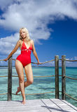 The young woman in a red bathing suit on sea background Royalty Free Stock Image