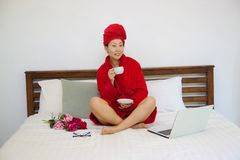 Young woman in red bathrobe on bed with laptop and cup. stock image