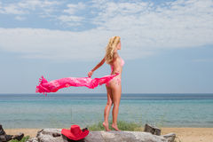 Young woman in red bikini holding sarong on the beach Royalty Free Stock Photography