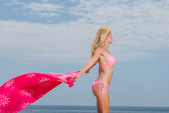 Young woman in red bikini holding sarong on the beach Royalty Free Stock Photos