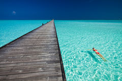 Young woman in red bikini swimming next to jetty in azure water. Of Maldives Royalty Free Stock Photos