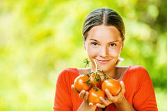 Young woman in red blouse with tomato Royalty Free Stock Photo