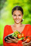 Young woman in red blouse with tomatoes, eggplants, peppers Royalty Free Stock Photo