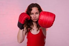 Young woman in red boxing gloves on a pink background. Active lifestyle, self-defense beautiful female girl person portrait studio fighter hand punch arm fist stock photo