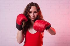 Young woman in red boxing gloves on a pink background. Active lifestyle, self-defense beautiful female girl person portrait studio fighter hand punch arm fist royalty free stock image