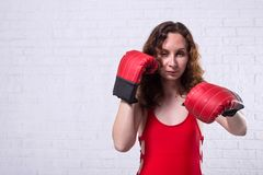 Young woman in red boxing gloves on a white brick background. Active lifestyle, self-defense beautiful female girl person portrait studio fighter hand punch royalty free stock photo