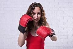 Young woman in red boxing gloves on a white brick background. Active lifestyle, self-defense beautiful female girl person portrait studio fighter hand punch stock image