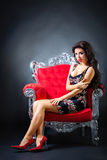 Young woman in a red chair. Retro style. Royalty Free Stock Image