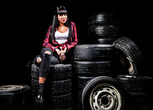 Young woman in a red checked shirt sitting on a tires Royalty Free Stock Photos