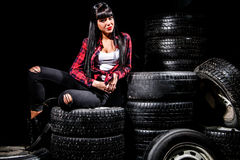 Young woman in a red checked shirt sitting on a tires Stock Image