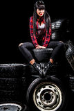 Young woman in a red checked shirt sitting on a tires Royalty Free Stock Photo