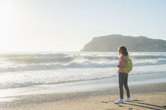 Young woman in red checkered shirt, jeans, white sneakers walking along beach and the stormy ocean on sunny winter day Stock Photo