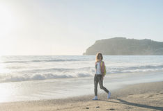 Young woman in red checkered shirt, jeans, white sneakers walking along beach and the stormy ocean on sunny winter day Royalty Free Stock Photography