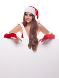 Young woman in red christmas dress and hat with an empty billboa Royalty Free Stock Photography