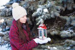Young woman with red Christmas lantern in the snow Royalty Free Stock Images