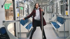 Young woman dancing in subway. Young woman in red coat dancing in subway stock video footage