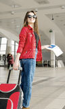 Young woman in a red coat and hat standing in the terminal or at the station with a suitcase and passport Royalty Free Stock Photography