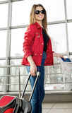 Young woman in a red coat and hat standing in the terminal or at the station with a suitcase and passport Stock Image