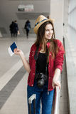 Young woman in a red coat and hat standing in the terminal or at the station with a suitcase and passport Stock Images