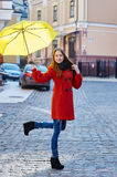 Young woman in a red coat with yellow umbrella walks through the city Royalty Free Stock Photo
