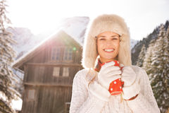 Young woman with red cup standing near cosy mountain house Stock Photos