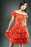 Young woman in red dress. Young Asian woman in red dress with gold details Royalty Free Stock Image