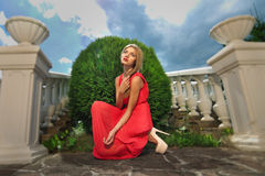 Young woman in a red dress Stock Images