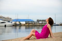 Young woman in a red dress ans curly hair sit on the water coast Royalty Free Stock Images