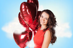 Young woman in red dress with balloons Stock Images