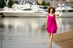 Young woman in a red dress and curly hair on the water coast Stock Image