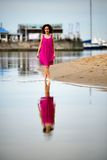 Young woman in a red dress and curly hair on the water coast Stock Photos