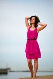 Young woman in a red dress and curly hair on the water coast Stock Photo