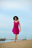Young woman in a red dress and curly hair on the water coast Royalty Free Stock Image