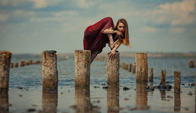 Young woman in red dress is dancing in water on sea background. royalty free stock photos