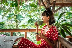 Young woman in red dress drinking a coffee in a tropical restaurant on Bali island. Travel, jungle, rainforest of Indonesia. stock photos