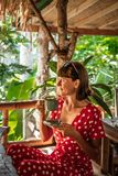 Young woman in red dress drinking a coffee in a tropical restaurant on Bali island. Travel, jungle, rainforest of Indonesia. royalty free stock image