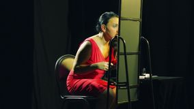 A young woman in a red dress in front of a mirror paints her eyelashes with black mascara. Overall plan stock footage