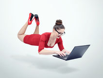 Young woman in red dress and glasses hovering in the air with laptop Stock Images