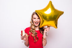 young woman in red dress with gold star shaped balloon smiling and drinking champagne Stock Photos