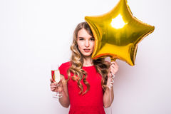 Young woman in red dress with gold star shaped balloon smiling and drinking champagne Royalty Free Stock Photography