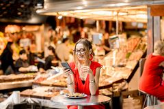 Woman eating mussels at the food market. Young woman in red dress having lunch with mussels and rose wine sitting at the food market royalty free stock photo