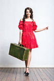 Young woman in a red dress and holding a suitcase Royalty Free Stock Photography