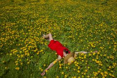 Young woman in red dress is laying on the grass full of yellow flowers. Woman in red shoe dress is enjoying the summer weather stock photography