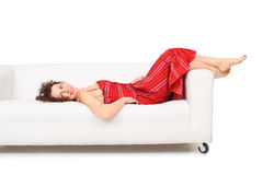 Young woman in red dress lies on white sofa Royalty Free Stock Photography