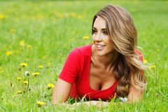 Young woman in red dress lying on grass Stock Photography