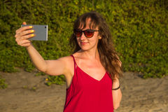 Young woman in red dress making selfie photo on a beach. North G Stock Photography