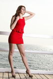 Young woman in red dress on the pier Royalty Free Stock Photography